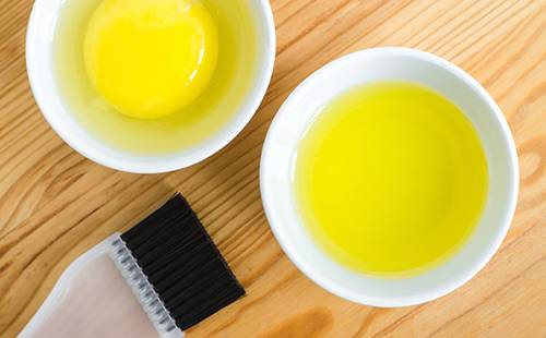 Масло и сырое яйцо разлиты в маленькие керамические плошки