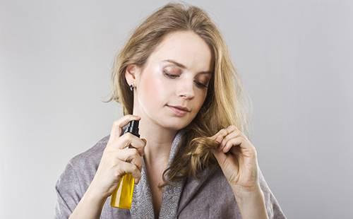 Девушка смачивает маслом кончики волос