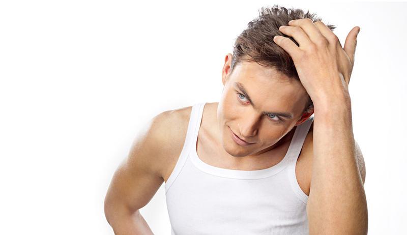мужчина трогает свои волосы